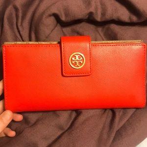 Orange Tory Burch wallet.